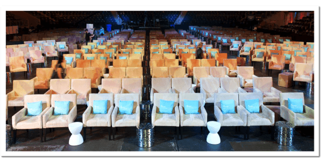 large meeting space with beige chairs and blue pillows facing a stage